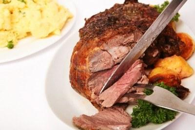 3563540-un-erbe-cosciotto-di-agnello-disossata-essere-scolpito-con-prezzemolo-e-patate-arrosto-sul-piatto-e-
